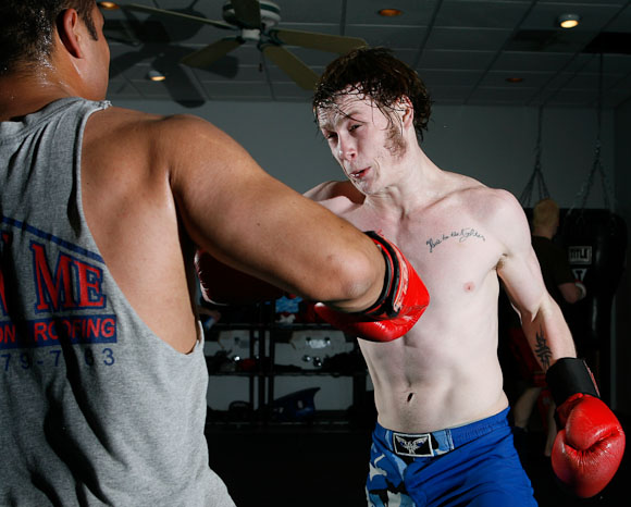 "Kevin Croom (right) takes a swing at Eric Ward during an evening practice at the Hulett House Gym in Columbia, Mo. on April 7, 2009, three days before their Midwest Fight League contests at the Blue Note.  Croom said that in a week before a big event, he ""…just wants to hit people."""