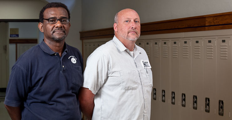 Anthony Fitzgerald, left, a Hickman High School custodian, and Arnold Cromwell, right, a custodian from Rock Bridge High School, stand in the hallways of Hickman High on Monday, September 21, 2009 in Columbia, Mo.  Despite the two schools' athletic rivalries, neither Fitzgerald or Cromwell take it too seriously.