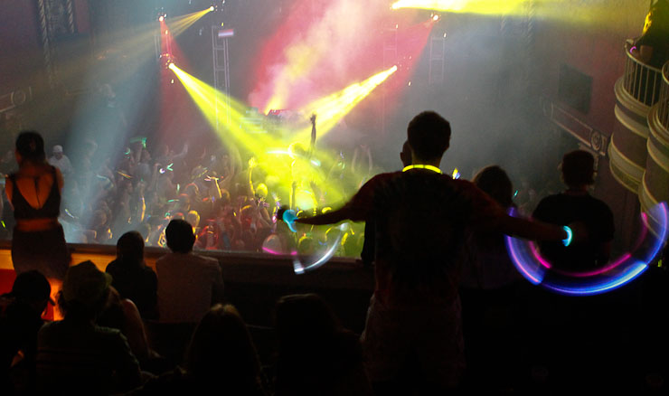 Fans wave glow sticks on the balcony of the Blue Note at the start of the Bassnectar concert, fashioned to be like a rave party.